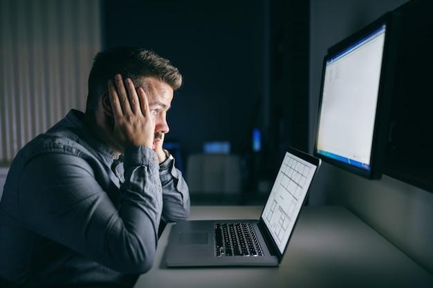 Müder junger kaukasischer angestellter, der kopf in händen hält und computermonitor betrachtet, während er spät in der nacht im büro sitzt.