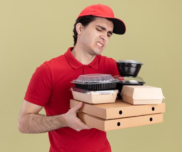 Müder junger kaukasischer liefermann in roter uniform und mütze, der pizzapakete mit lebensmittelbehältern und papiernahrungspaketen auf ihnen einzeln auf olivgrüner wand hält und betrachtet