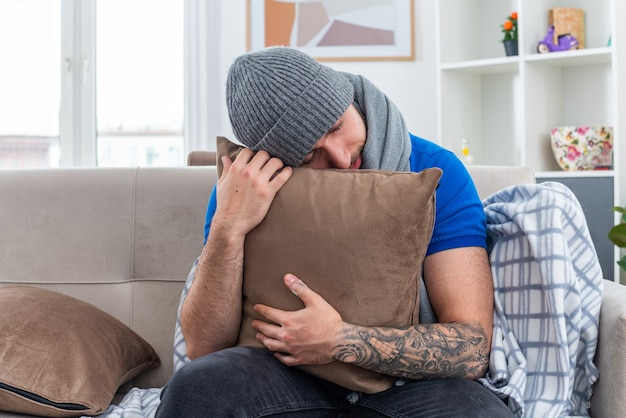 Müder junger kranker mann mit schal und wintermütze sitzt auf dem sofa im wohnzimmer und umarmt das kissen, das den kopf mit geschlossenen augen darauf ruht