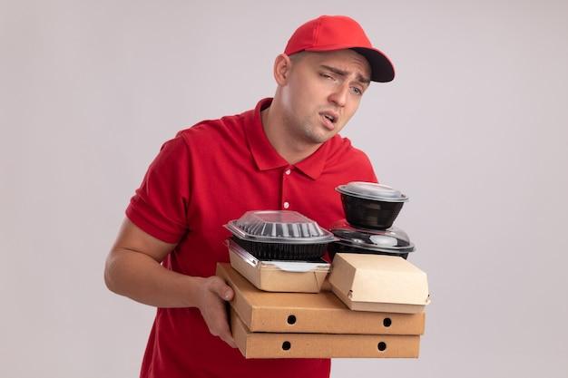 Müder junger lieferbote, der uniform mit kappe trägt, die lebensmittelbehälter auf pizzaschachteln isoliert auf weißer wand hält