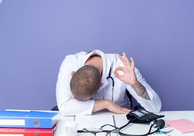 Müder junger männlicher arzt, der medizinische robe und stethoskop trägt, sitzt am schreibtisch mit arbeitswerkzeugen, die kopf auf schreibtisch setzen und ok zeichen lokalisiert auf lila hintergrund tun
