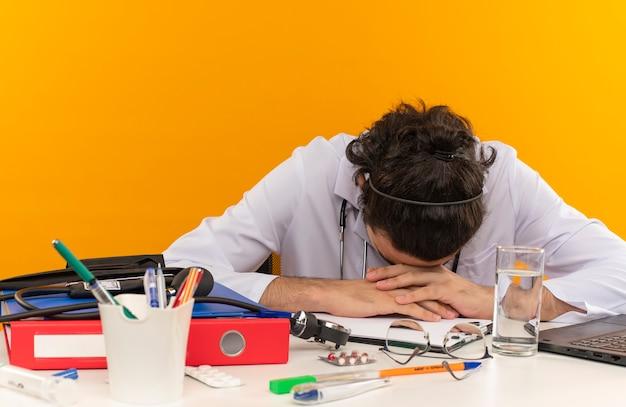 Müder junger männlicher arzt mit medizinischer brille im medizinischen gewand mit stethoskop, das am schreibtisch sitzt, arbeit am laptop mit medizinischen werkzeugen senkte seinen kopf auf isolierte gelbe wand mit kopierraum