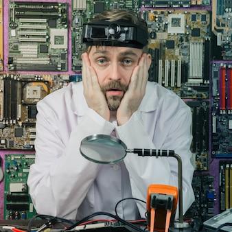 Müder junger männlicher elektrikeringenieur, der am schreibtisch des elektrischen labors sitzt.