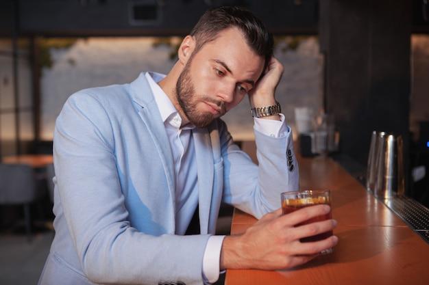 Müder junger mann, der allein an der bar trinkt. einsamer gutaussehender mann, der im nachtclub etwas trinkt