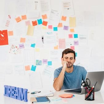 Müder junger mann, der nahe laptop gegen wand mit anmerkungen sitzt