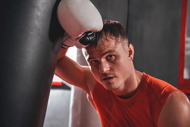 Müder junger mann in sportbekleidung trainiert hart auf schwerem boxsack. muskulöser sportler mit weißen boxhandschuhen, die wegschauen, während sie in der boxhalle stehen