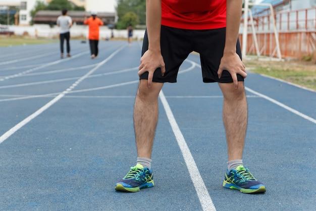 Müder junger mann läufer, der eine pause nach dem laufen macht. workout-konzept