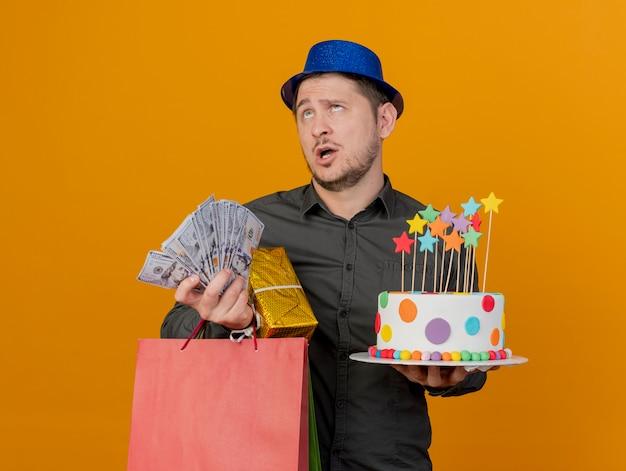 Müder junger party-typ, der blauen hut trägt, der geschenke mit kuchen und geld auf orange isoliert hält