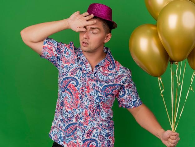 Müder junger party-typ mit geschlossenen augen, der rosa hut trägt, der ballons hält und handgelenk auf stirn lokalisiert auf grün setzt