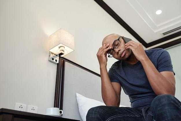 Müder junger schwarzer mann, der unter kopfschmerzen leidet und mit verwandten, freunden oder kollegen telefoniert