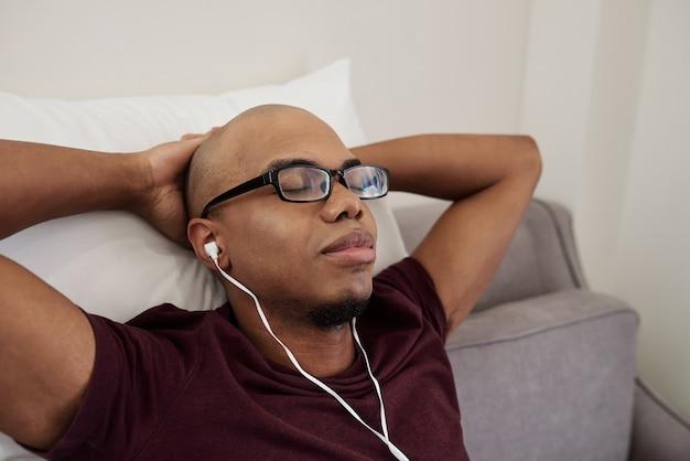 Müder junger schwarzer mann in brille, der die augen schließt, wenn er sich auf dem sofa entspannt und gute musik in den ohrhörern genießt