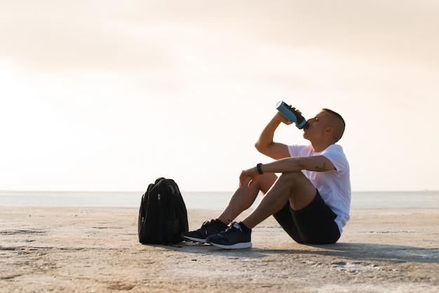 Müder junger sportler trinkt wasser auf dem boden