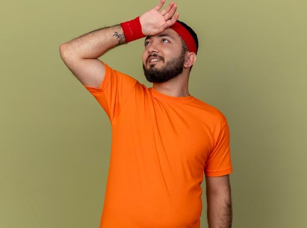 Müder junger sportlicher mann, der das tragen des stirnbandes und des armbandes abwischt, das stirn mit hand lokalisiert auf olivgrünem hintergrund abwischt