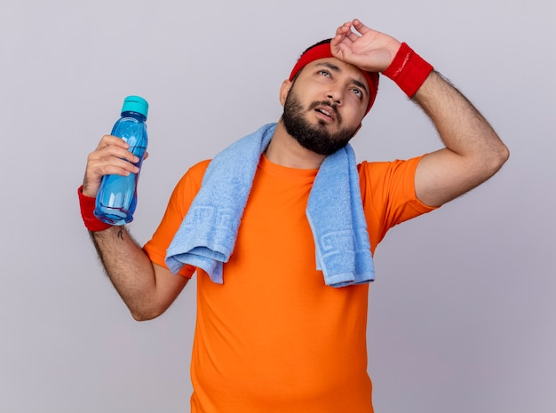 Müder junger sportlicher mann, der das tragen des stirnbandes und des armbandes hält, die wasserflasche mit handtuch auf schulter halten hand auf stirn lokalisiert auf weißem hintergrund halten