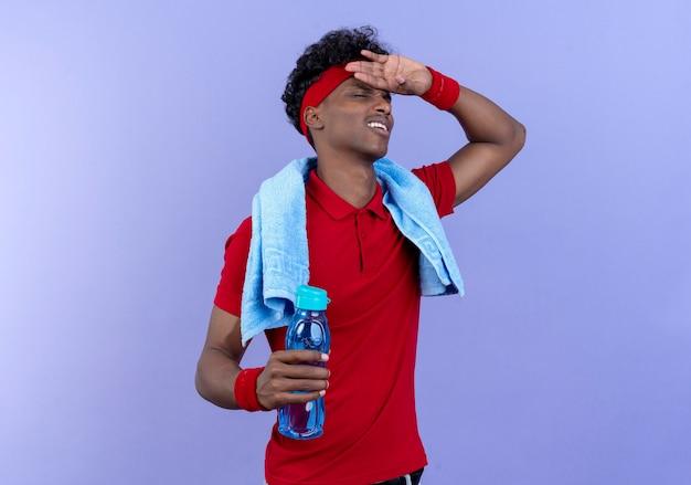Müder junger sportlicher mann, der stirnband und armband-putting-hand trägt