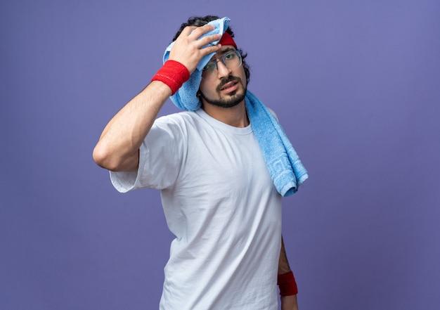 Müder junger sportlicher mann mit stirnband mit armband, das die stirn mit einem handtuch abwischt