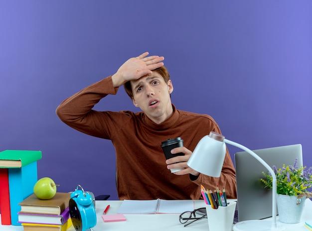 Müder junger studend junge, der am schreibtisch mit schulwerkzeugen sitzt, die tasse kaffee halten und hand auf stirn auf purpur legen