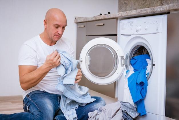 Müder kahlköpfiger mann, der mit schmutziger wäsche in der waschmaschine sitzt