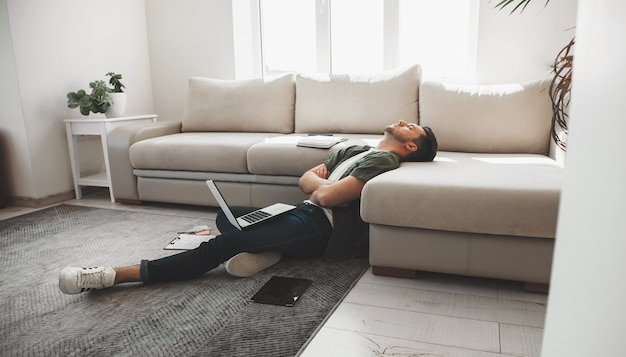 Müder kaukasischer mann, der auf dem boden mit einem computer und einem tablett mit gekreuzten händen einschlafen