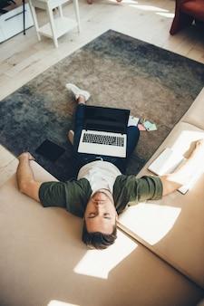 Müder kaukasischer mann mit der borste, die auf boden und sofa liegt, nachdem er am laptop mit einem buch gearbeitet hat