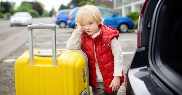 Müder kleiner junge bereit zum gehen zur autoreise mit seinen eltern