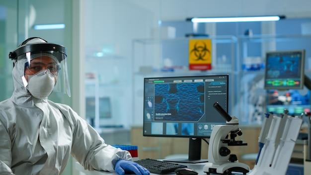 Müder laborarzt mit overall, der am computer arbeitet und in die kamera schaut. wissenschaftler, der die virusentwicklung mit hightech, chemischen werkzeugen für wissenschaftliche forschung und impfstoffentwicklung untersucht