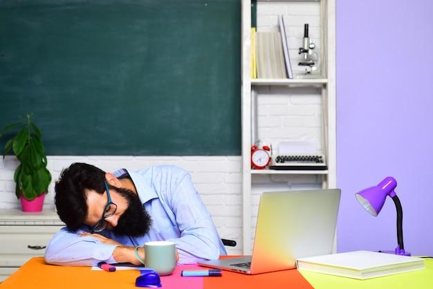 Müder lehrer, der im klassenzimmer schläft, der sich auf die universitätsprüfungen vorbereitet
