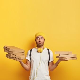 Müder lieferbote mit pizzaschachteln