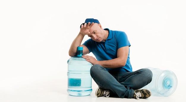 Müder lieferbote mit wasserflasche und kopienraum