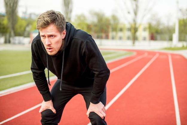 Müder männlicher athlet, der auf rennstrecke steht