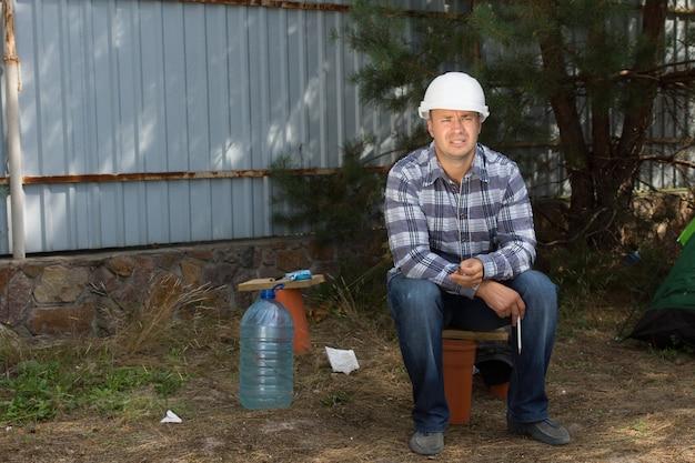 Müder männlicher bauingenieur, der an der ecke in der baustelle sitzt, während er den baufortschritt betrachtet.