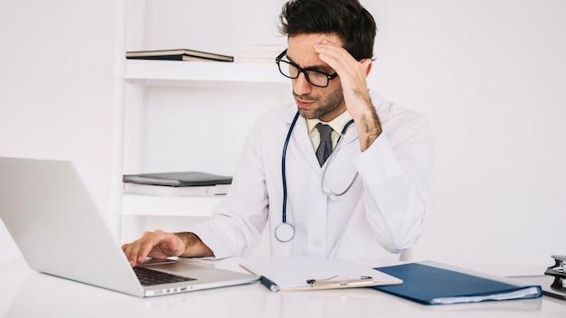 Müder männlicher doktor, der an laptop in der klinik arbeitet