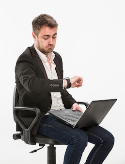 Müder manager sitzt auf einem stuhl und arbeitet mit einem laptop, der auf seine uhr auf seiner rechten hand schaut. studio, weißer hintergrund.