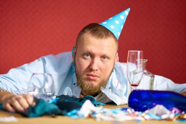 Müder mann am tisch mit blauer mütze in einem unordentlichen zimmer nach der geburtstagsfeier