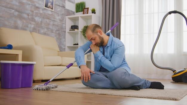 Müder mann, der auf einem gemütlichen teppich sitzt, nachdem er den raumboden mit mopp und reinigungsmittel gereinigt hat.