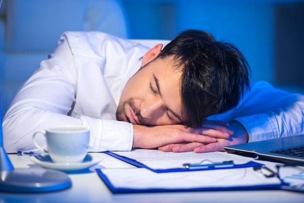 Müder mann, der bei der arbeit mit computer schläft.