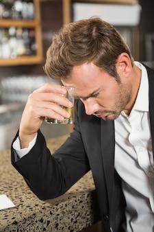 Müder mann, der einen whisky isst