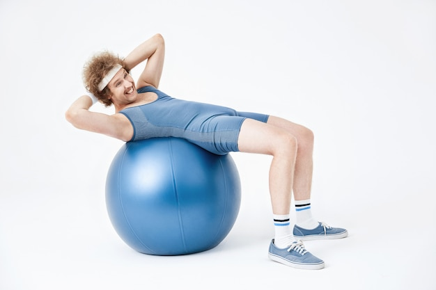 Müder mann, der sich auf übungsball zusammenrollt. sieht erschöpft aus