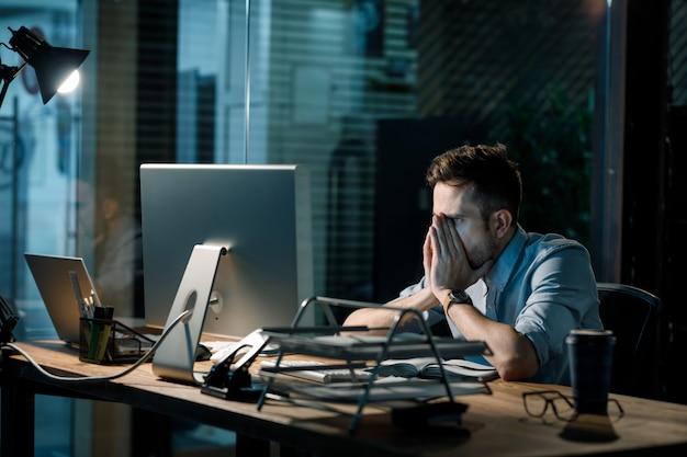 Müder mann, der spät im büro arbeitet