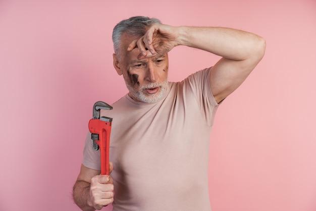 Müder mann mit einem schraubenschlüssel in den händen packte seinen kopf