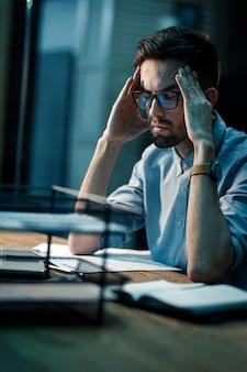 Müder mann mit kopfschmerzen im büro