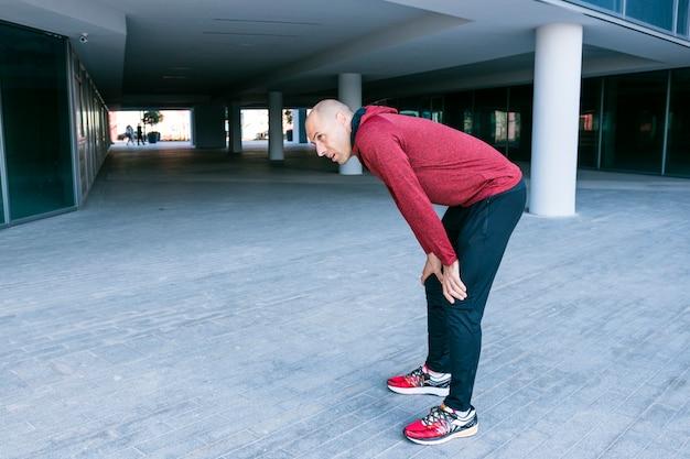 Müder mannläufer, der eine pause macht, nachdem er stark gelaufen ist