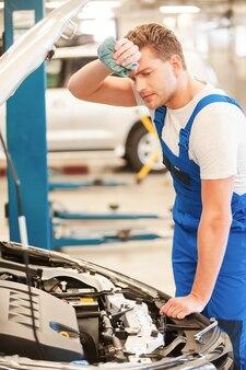 Müder mechaniker. müder junger mann in uniform, der auto untersucht und sich die stirn mit lappen abwischt, während er in der werkstatt steht