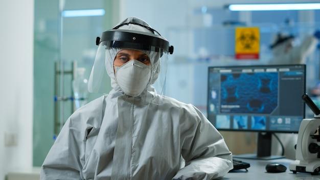 Müder mikrobiologe im overall, der im labor sitzt und in die kamera schaut. team von wissenschaftlern, die die virusentwicklung mit hightech- und chemiewerkzeugen für wissenschaftliche forschung und impfstoffentwicklung untersuchen.