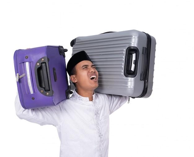 Müder muslimischer mann, der zwei schwere koffer auf seiner schulter trägt