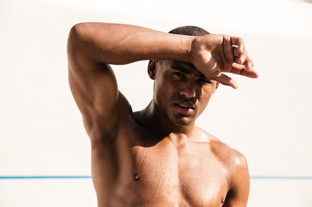 Müder nasser athletischer afrikanischer mann, der schweiß mit seiner hand abwischt