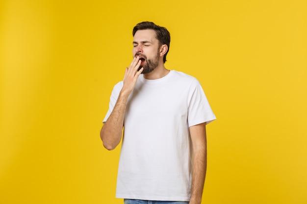 Müder oder gelangweilter junger mann aus dem kaukasischen hipster, der beim gähnen den mund bedeckt und sich nach einem anstrengenden arbeitstag erschöpft fühlt