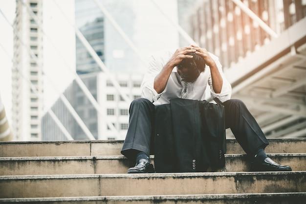 Müder oder gestresster geschäftsmann, der auf dem gehweg in der stadt nach seiner arbeit sitzt.
