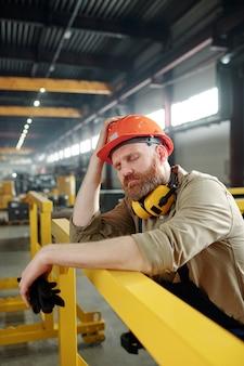 Müder oder kranker ingenieur in arbeitskleidung und helm, der sich an die bar lehnt, während er mitten am arbeitstag in der fabrik eine pause macht