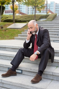 Müder reifer geschäftsmann, der über mobiltelefon spricht